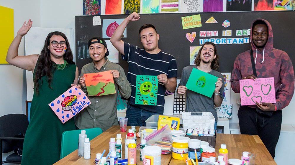 group holding their artwork